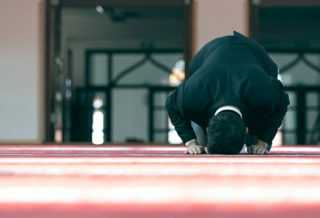 Man Praying mosque red carpet