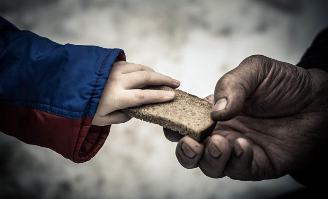 Child hands bread to poor person